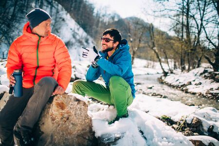 Two young male tourists talk while drinking coffee near a river in the mountains. Beautiful winter landscape with snow covered banks and trees on background. Climbing, trekking, active life concept