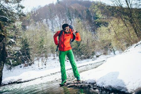 Young male tourist takes off his backpack near a river in the mountains.Beautiful winter landscape with snow covered banks and trees  on background. Climbing, hiking, trekking, active life concept.