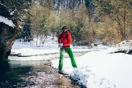 Young male tourist crosses a river in the mountains.Beautiful winter landscape with snow covered banks and trees  on background.Climbing, trekking  and active life concept. Hiking, camping equipment.