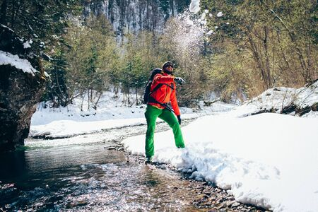 Young male tourist throws snow near a river in the mountains.Beautiful winter landscape with snow covered banks and trees  on background. Climbing trekking  and active life concept. Hiking equipment.