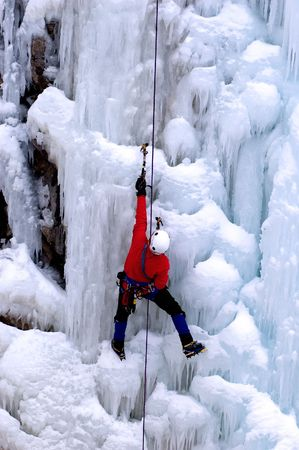 techincal: ice climber in red coat on self belay reaching for higher ground Stock Photo