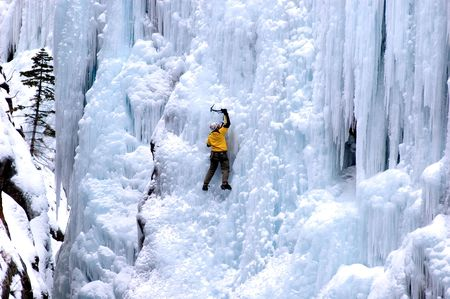 techincal: ice climber in yellow coat soloing on large ice wall