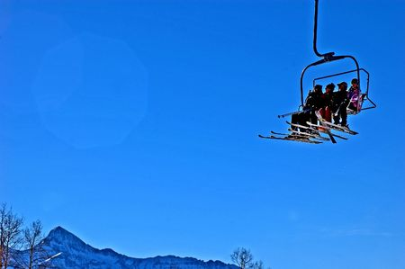 skiers: skiers on chairlift with mt wilson in distance Stock Photo