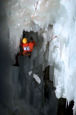 competitve ice climber on route with falling ice