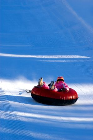 child sledding down hill on innertube