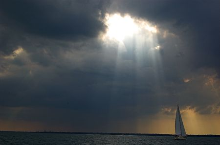storm clouds: sloop sailboat avoiding storm