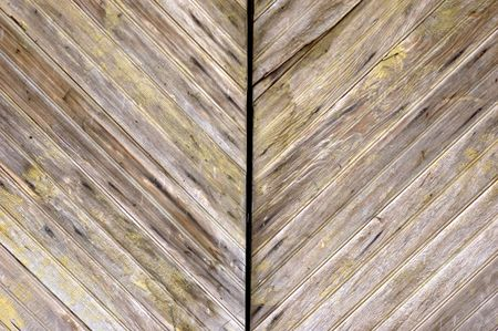 angled wood panelled garged doors with aged patina