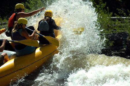 yellow raft breaking through the top of river wave from rear Stock Photo