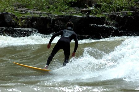 full wetsuited surfer river surfing