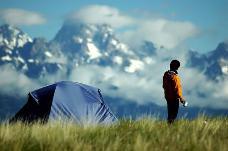 adult male standing in field looking at scenic mountain vista
