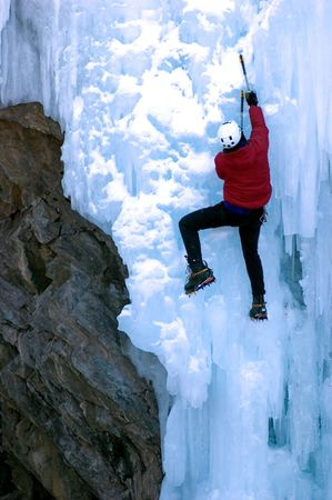 adult male climbing steep ice un red coat Stock Photo