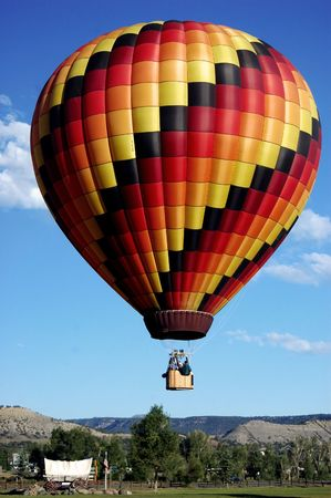covered wagon: hot air balloon lifting off above old west covered wagon