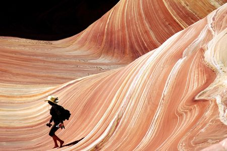 barefoot cowboy: woman in cowboy hat running down wave of sandstone