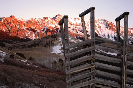 vintage cattle loading gate and flaming red mountains