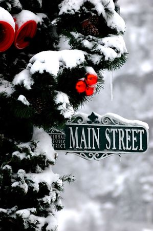 christmas decorated street sign pole on snowy winter day