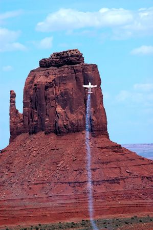 acrobatic airplane in vertical flight with East Mitten in background