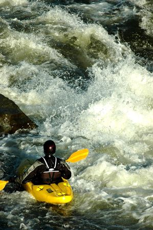 adult male in yellow kayak looking back on descent he just ran
