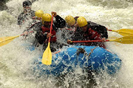 five people in blue raft splashing through river rapid Reklamní fotografie