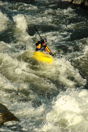 adult male in yellow kayak descending class IV whitewater rapids
