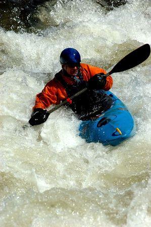 male wearing orange spray coat in blue kayak in class IV whitewater Stock Photo