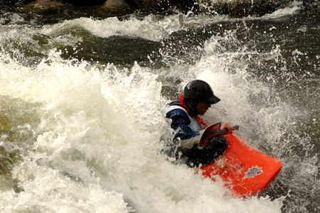 competitor in kayak rodeo on river wave