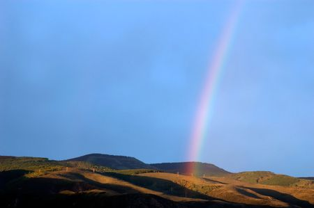 vertical stripe of rainbow over mountain valley
