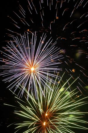 multiple colored star fireworks exploding simutaenously with blue tracers