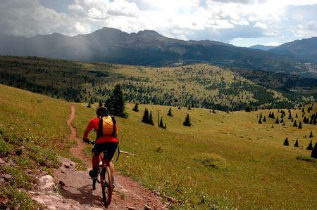 moteros: bicicleta de monta�a �nico piloto en pista en pista de las Monta�as Rocosas con tormenta en la distancia  Foto de archivo