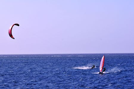 kite boarder and windsurfer side by side on caribbean blue sea Stock Photo