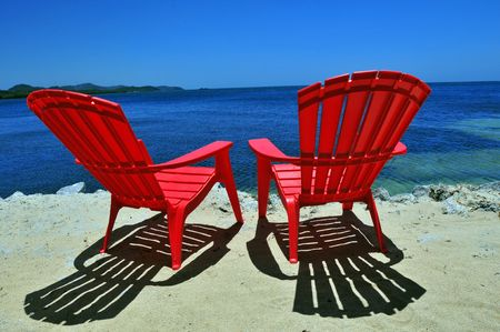 two red beach chairs on white sand with caribbean sea view Stock Photo