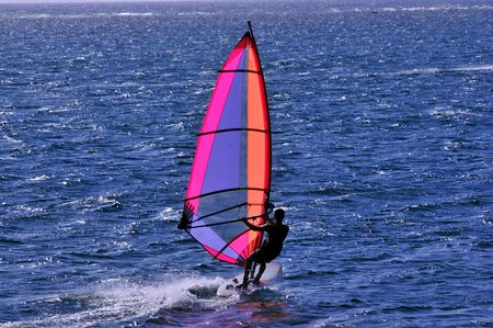 windsurfer with bright colored sail on caribbean blue water