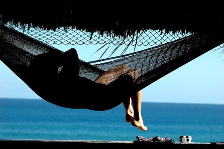 woman laying in hammock viewing the ocean