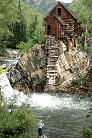 19th century: man fishing pool below the crystal mill, an iconic 19th century example of colorado mining architecture