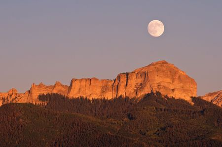 Summer full moon rising over Courthouse Rock a prominent feature in the Cimmarron Mountains Stock Photo