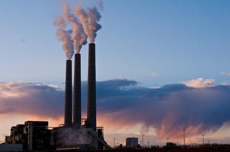 industrial landscape of coal burning smokestacks at sunset