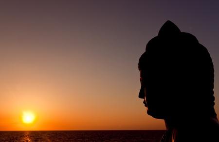 silhouette of buddha watching sunset Stock Photo