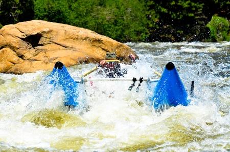 mature male rowing cataraft through class III rapid
