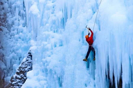 ice climbing: Athletic man in red coat with orange helmet and gold ice tools climbing a large blue wall of ice in the Uncomphagre Gorge
