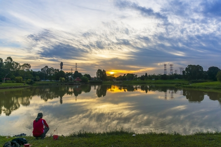outdoorsman: Fishing with sunset reflection background Stock Photo