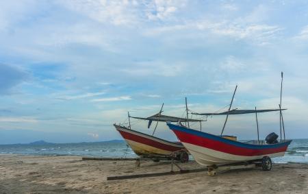 pahang: Traditional wooden boat at sea shore with blue skies