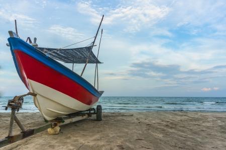 cielos azules: Barco tradicional de madera en la orilla del mar con el cielo azul