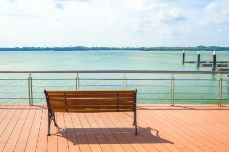 cielos azules: Silla de madera frente al mar con el cielo azul