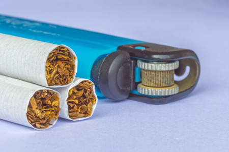 Yellow filter cigarette with blurred lighter macro background photo