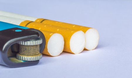 Yellow filter cigarette with blurred lighter macro foreground photo