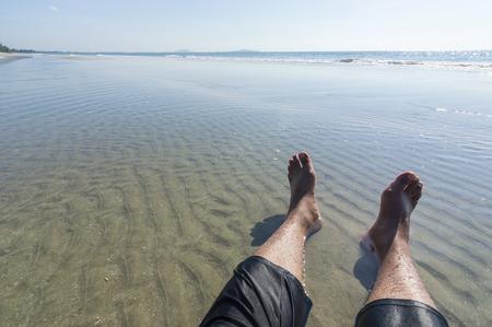 piernas hombre: Piernas del hombre en la playa con la luz del sol directa