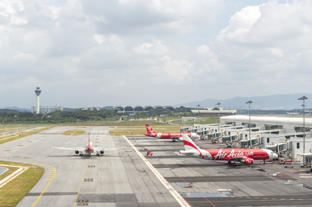 embark: KUALA LUMPUR, MALAYSIA -  DECEMBER 10, 2014:Air Asia Airplanes at KLIA2 airport. Air Asia is a fast growing low cost carrier based in Malaysia.