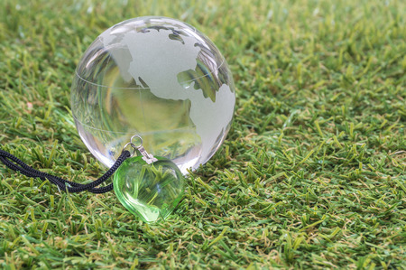transparent globe: Transparent globe and green heart with green grass background Stock Photo