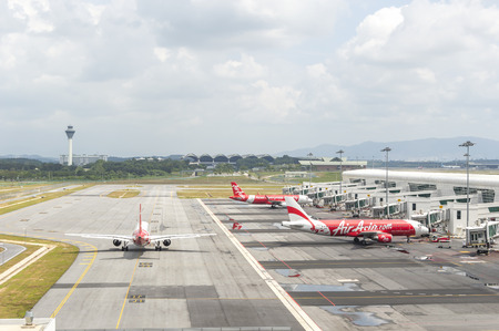 famous industries: KUALA LUMPUR, MALAYSIA -  DECEMBER 10, 2014:Air Asia Airplanes at KLIA2 airport. Air Asia is a fast growing low cost carrier based in Malaysia.