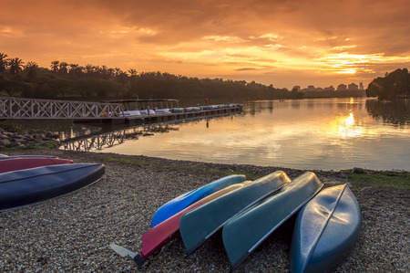 A bunch of kayaks stranded with a orange sunset background photo