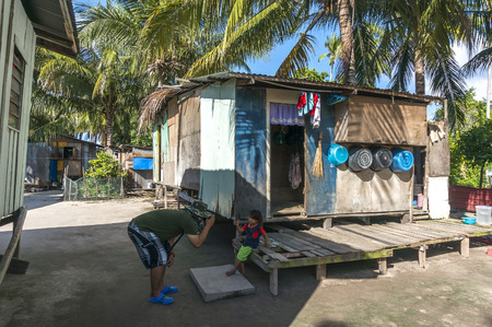 sabah: SABAH, MALAYSIA - AUGUST 16, 2016 : A view of poor wooden house and people at Mabul Island, Sabah Malaysia.